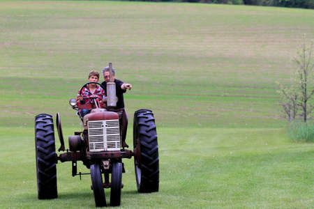 Farmer teaches his grandson to drive a tractor photo