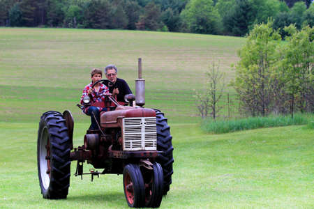 Opa the Farmer teaches his grandson to drive a tractor photo