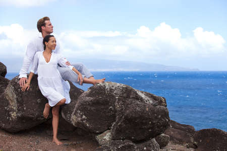 Love on the rocks Newleyweds in Hawaii above the ocean on a Lava bluff photo