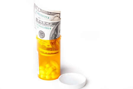 Prescription Drugs in a container with a hunderd dollar bill and a fifty isolated on white Stock Photo - 17354592