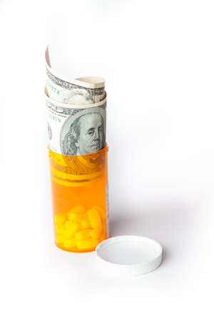 doctor with money: Prescription Drugs in a container with a hunderd dollar bill and a fifty isolated on white