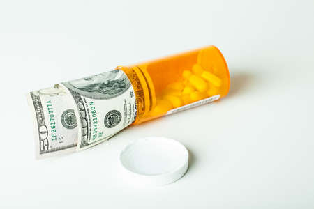 Prescription Drugs in a container with a hunderd dollar bill and a fifty isolated on white Stock Photo - 17354593