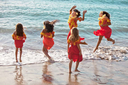 rural community: Group of five Polynesian Hula girls  in joyful Friendship jumping in the Pacific Ocean of Hawaii
