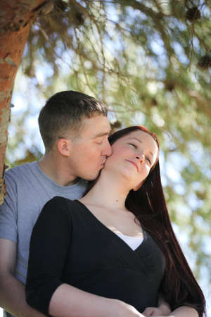 Man kissing his fiance on the neck photo