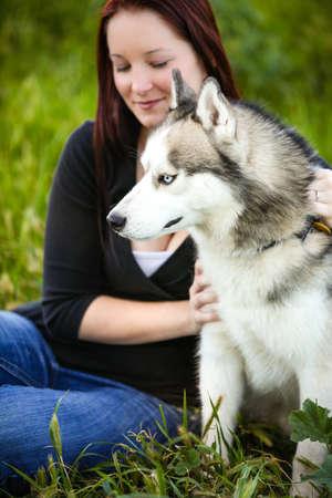 Retrato de un perro Siberian Husky hermoso al aire libre con su dueño mujer detrás de él Foto de archivo - 17456595