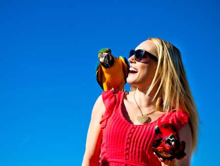 guacamaya: Mujer hermosa con los loros guacamayos risa con entusiasmo contra un cielo azul hermoso