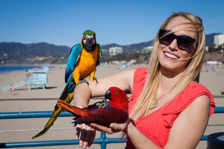 Macaw Parrots on Santa Monica Pier California beautiful Woman tourist and blue sky