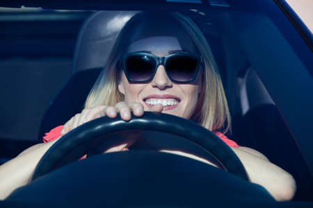 Pretty blonde woman behind steering wheel of a sports car with a big smile Stock Photo - 17492492