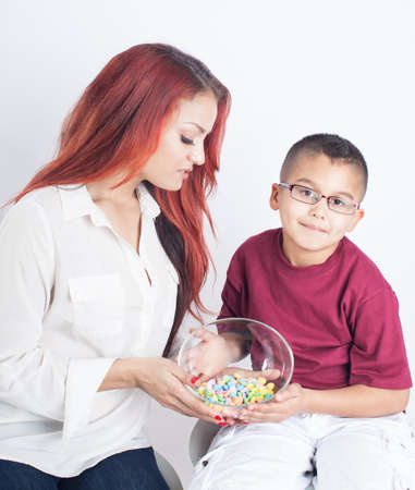 Valentine's day Pretty young mom and her son with a bowl of heart shaped candies photo