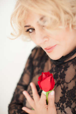 Maature Beautiful Blonde woman holding a rose looking at camera