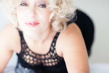 Mooie Sexy Blonde rijpe vrouw in zwarte lingerie Stockfoto