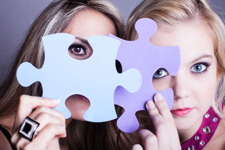 Two Beautiful women looking through game pieces at camera Stock Photo - 17576927