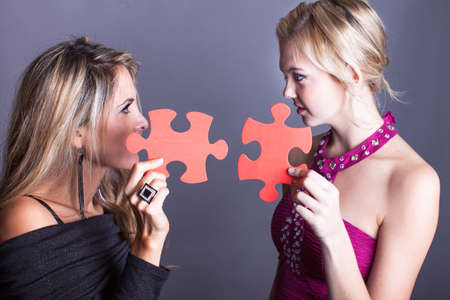Two Beautiful women looking at each other with puzzle pieces photo