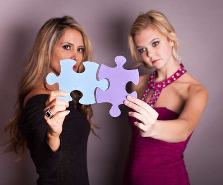 Two Beautiful women looking through game pieces at camera Stock Photo - 17576925