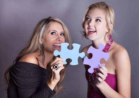 Two Beautiful women laughing as they hold the answer to the puzzle photo
