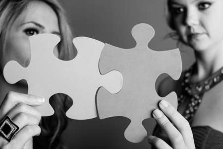 Two Beautiful women holding out puzzle pieces in a black and white image photo