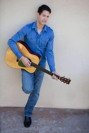 Handsome guy in his thirties with acoustic guitar photo
