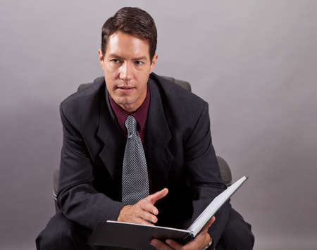 Handsome business man isolated on gray sitting with a notebook Stock Photo - 17641648