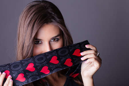 Brunette Beautiful Woman holding a necktie with hearts and XOXO on to isolate her warm inviting eyes Stock Photo - 17789639