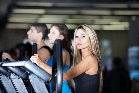 Beautiful Woman with long hair and her friends at the Gym on stair steppers photo