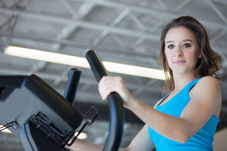 Attractive young woman in Blue at the Gym on stair steppers photo
