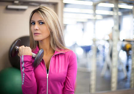 Attractive Woman in her thirties with long blonde hair exercising with weights photo