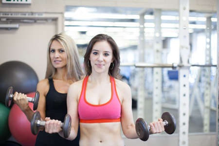 Beautiful attractive woman beinng trained at a gym photo