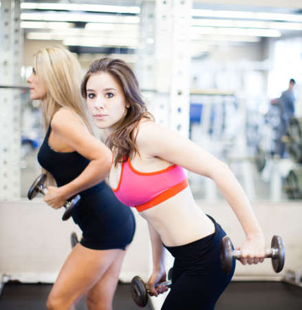 Women working on their triceps with dumbells at the gym photo
