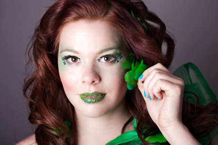 Red headed Beautiful woman  with a shamrock wearing exotic green makeup Stock Photo - 18008820