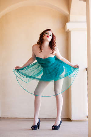 Beautiful red headed girl in a turquoise party dress for spring time photo