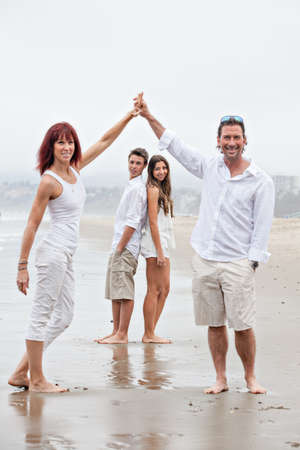 Mother and father holding arms up with their teenagers framed between them Standard-Bild