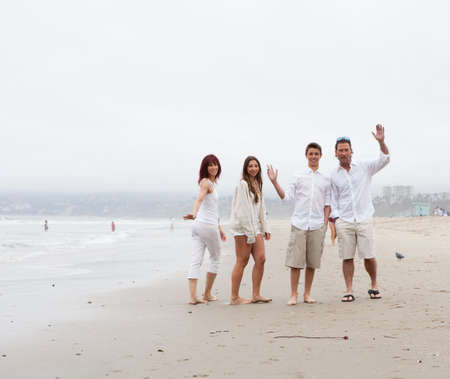 Attractive family with teens  standing together on the beach at Santa Monica Ca photo