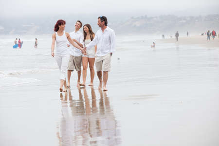 Happy family of four with teens walking and talking on the beach at Santa Monica Ca