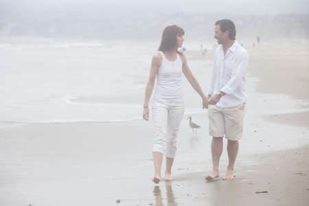 In Love gorgeous Couple walking on beach hand in hand smiling and talking photo