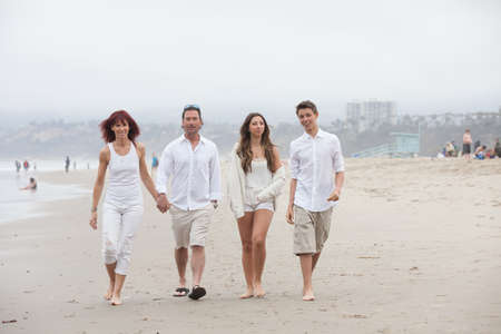 four person: Good looking family with teens walking and talking on the beach at Santa Monica Ca