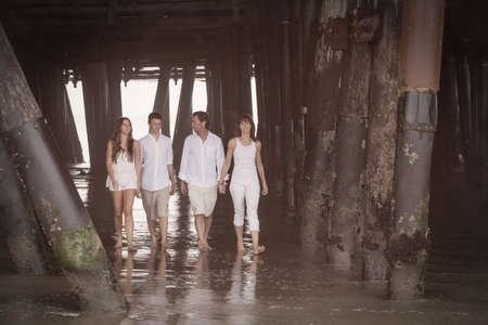 Attractive Family walking along the beach under the Santa Monica pier photo