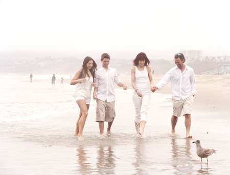 Good looking family with teens walking and talking on the beach at Santa Monica Ca photo