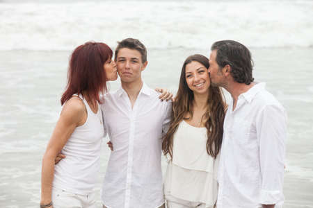 Good looking family kissing each other in show of affection photo
