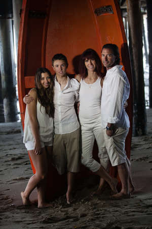 Beautiful Family with teenagers   posing for a Portrait by life boat photo