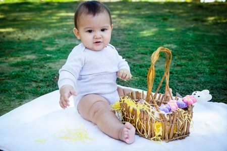 play ground: Baby on a blanket in the park with an Easter basket