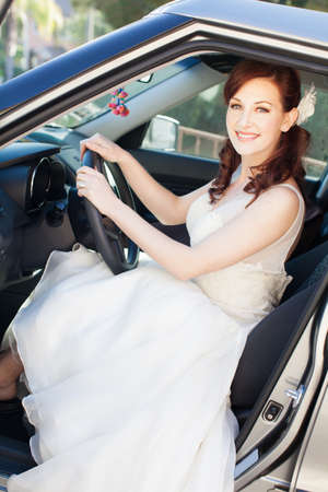 Beautiful woman in her car all dressed up photo