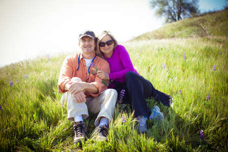 retirement: Attractive Middle aged couple lying in the tall grass and Wild Lupine Stock Photo