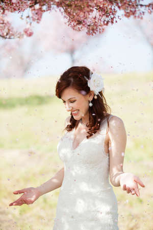Beautiful laughing bride showered by cherry blossom confetti photo