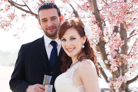 beautiful bride: Newlyweds having a Champagne Toast in nature under a blooming cherry tree