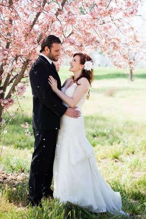 fleurs de cerisiers: Belle mari�e et le mari� heureux d'�tre douch�s avec des confettis de fleurs de cerisier