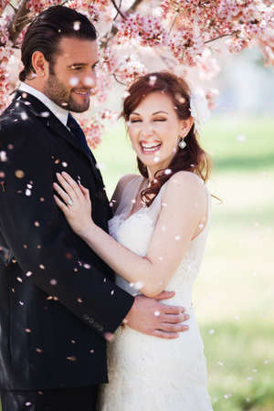 Beautiful happy bride and groom being showered with confetti from cherry blossoms