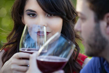 Happy Beautiful Young Couple toasting looking into each others eyes photo
