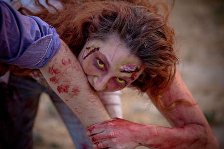 Zombie woman outside with yellow eyes looking at camera biting a victim photo