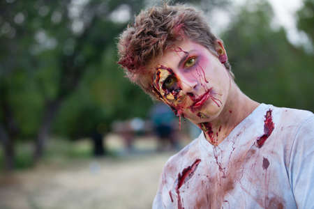 Zombie teen outside with yellow eyes looking at camera photo