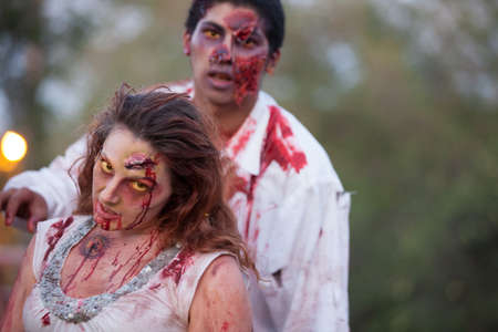 Zombie man and  woman outside with yellow eyes looking at camera photo